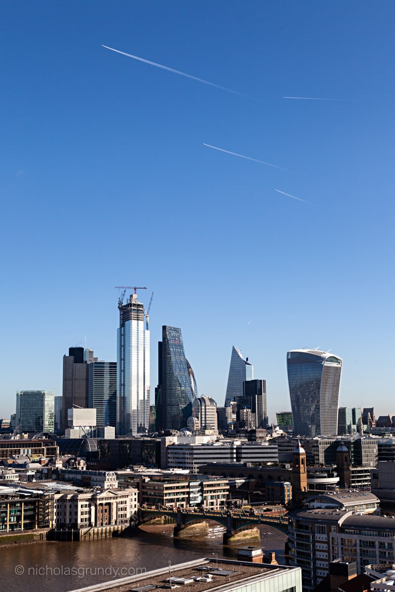 Photo of City of London Skyscrapers with jet trails overhead